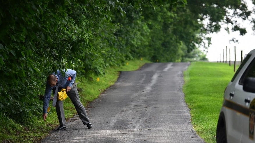 Investigator places evidence flags along the driveway of a home on Spring Valley Road in Quarryville, Pa. (Casey Kreider/LNP via AP)