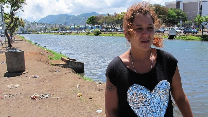 FILE - In this Tuesday, June 9, 2015 file photo, Stefanie Sanchez talks about what it's like to live along the banks of a canal in Honolulu. Sanchez has lived in a tent here for several months, and the city of Honolulu sent a crew to clean up the area on Tuesday. Sanchez said she planned to return after the sweep. Hours after a city crew cleared the banks of the canal, the homeless people that had been living there moved right back to the riverside, leaving some wondering whether the expense of taxpayer money was justified. (AP Photo/Cathy Bussewitz)