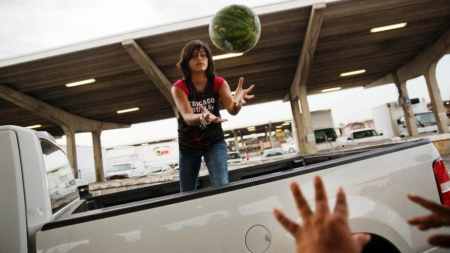 In this June 6, 2015, photo, Ailyn Lopez, 13, catches a watermelon from her mother Maria Cantellano as they load up a customer's pickup truck at their stand at the Atlanta Farmers Market in Atlanta. The Labor Department reports on U.S. producer price inflation in May on Friday, June 12, 2015. (AP Photo/David Goldman)