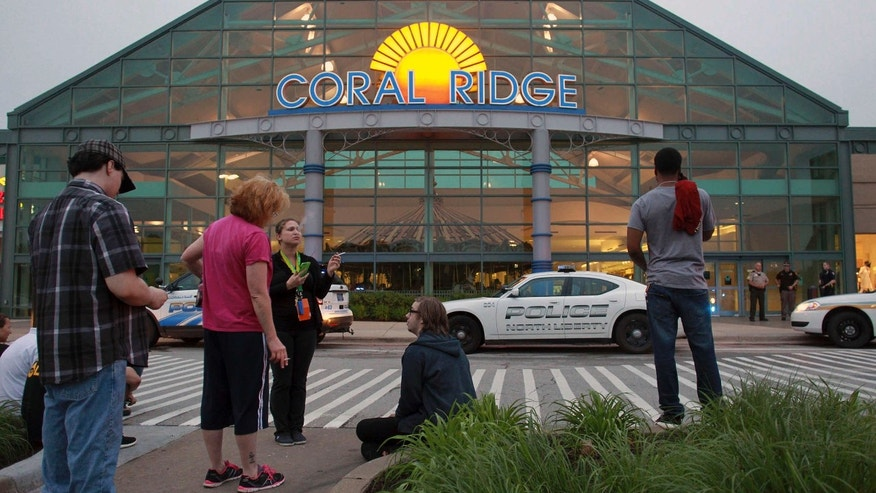 June 12, 2015: Shoppers and employees wait outside the Coral Ridge Mall following a shooting.
