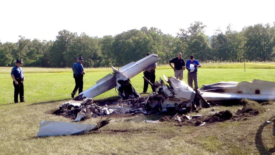 June 12, 2015: In this photo provided by The Houston Herald, authorities investigate a plane crash near Huggins, Mo.