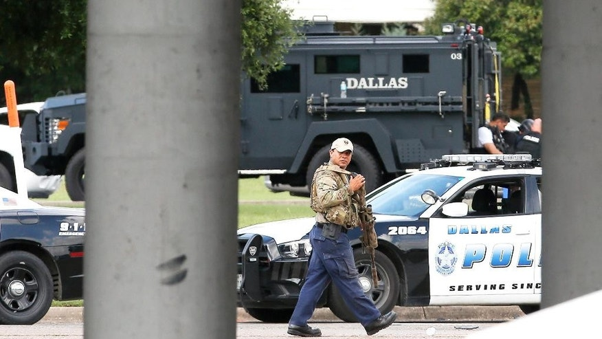 A sniper walks by the intersection of Dowdy Ferry Rd and Interstate 45 during a stand off with a gunman barricaded inside a van near by, Saturday, June 13, 2015, in Hutchins, Texas. The gunman allegedly attacked Dallas Police Headquarters. (AP Photo/Brandon Wade)