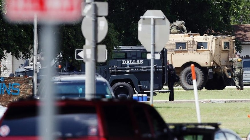 Law enforcement tactical vehicles are positioned near a gunman barricaded inside and armored van during a stand off, Saturday, June 13, 2015, in Hutchins, Texas. A police sniper shot a cornered suspect in an overnight attack on the Dallas Police Department's headquarters, and authorities were checking Saturday to see if he was alive or dead. (AP Photo/Brandon Wade)
