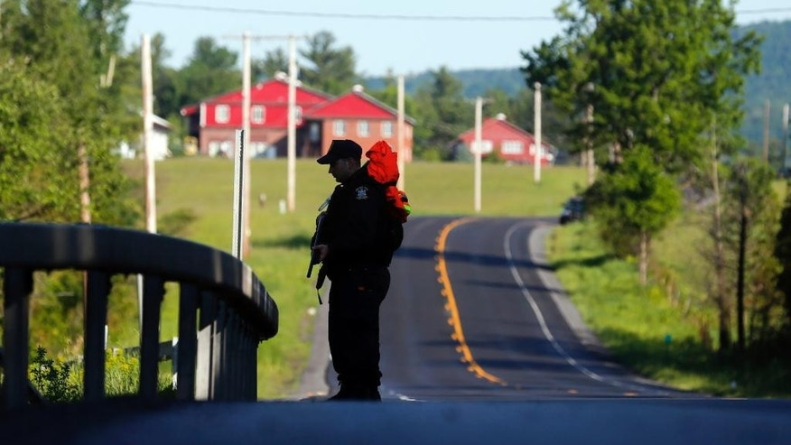 A law enforcement officer stands on Route 374 on Saturday, June 13, 2015, near Dannemora, N.Y.  Hundreds of law enforcement personnel have begun an eighth day searching for David Sweat and Richard Matt, two killers who used power tools to cut their way out of Clinton Correctional Facility in Dannemora in northern New York. (AP Photo/Mike Groll)
