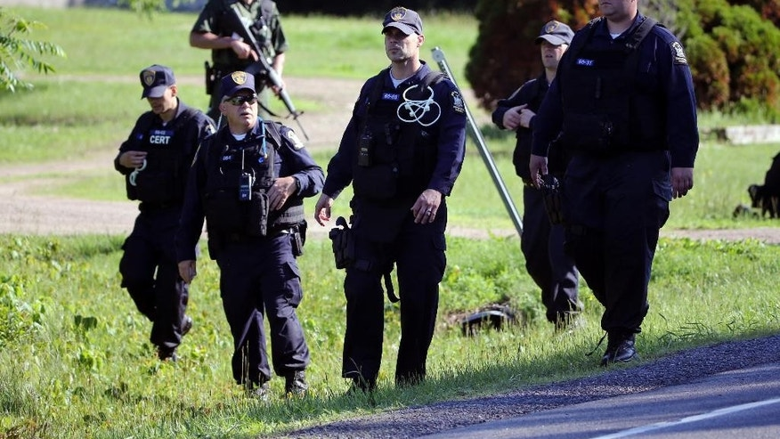 Law enforcement officers walk along Route 3 on Saturday, June 13, 2015, in Saranac, N.Y. Hundreds of law enforcement personnel have begun an eighth day searching for David Sweat and Richard Matt, two killers who used power tools to cut their way out of Clinton Correctional Facility in Dannemora in northern New York. (AP Photo/Mike Groll)