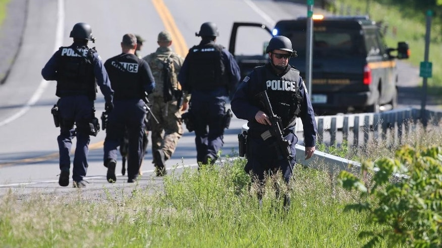 Law enforcement officers search along Route 3 on Saturday, June 13, 2015, in Saranac, N.Y. Hundreds of law enforcement personnel have begun an eighth day searching for David Sweat and Richard Matt, two killers who used power tools to cut their way out of Clinton Correctional Facility in Dannemora in northern New York. (AP Photo/Mike Groll)