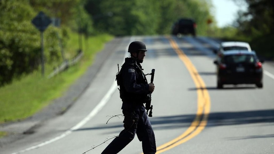 A law enforcement officer walks across Route 3 on Saturday, June 13, 2015, in Saranac, N.Y. Hundreds of law enforcement personnel have begun an eighth day searching for David Sweat and Richard Matt, two killers who used power tools to cut their way out of Clinton Correctional Facility in Dannemora in northern New York. (AP Photo/Mike Groll)