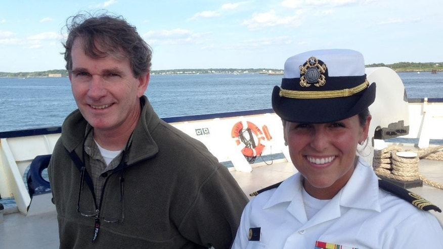 Michael Hurley, a South Carolina author who lost his storm-battered sailboat on a failed Atlantic crossing, left, poses for a photo with Maine Maritime Academy junior Gabrielle Wells on the stern of the training vessel State of Maine, Saturday, June 13, 2015, in Portland, Maine. Wells was student officer of the deck when Hurley's distress call was received Wednesday, leading to Hurley's rescue around 500 miles south of Newfoundland. (AP Photo/David Sharp)