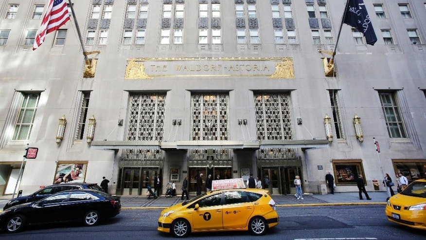 FILE - In this Oct. 6, 2014 file photo, a taxi passes in front of the fabled Waldorf Astoria hotel in New York. A police source said a wedding guest's gun went off accidentally at New York's Waldorf Astoria Hotel, Saturday, June 13, 2015, and a few people suffered minor injuries from debris. (AP Photo/Mark Lennihan, File)