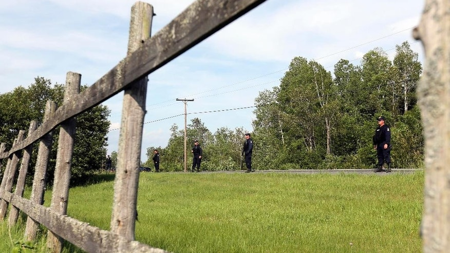 Law enforcement officers line up on Route 3 before returning to the woods while searching two prisoners who escaped from the Clinton Correctional Facility on Saturday, June 13, 2015, in Saranac, N.Y. Authorities are in the eighth day of searching for David Sweat and Richard Matt, two killers who used power tools to cut their way out of the prison in northern New York. (AP Photo/Mike Groll)