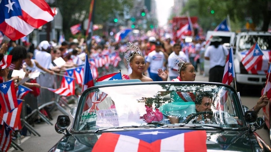 Jayda Vazquez, 12, left, and Kaylee Vazquez, 8, wave from atop a convertible in the procession as the annual National Puerto Rican Day Parade makes its way up New York's Fifth Ave., Sunday,  June 14, 2015. Hundreds of thousands of people turned out for the parade which celebrates the heritage and identity of Puerto Ricans living in New York. (AP Photo/Kevin Hagen)