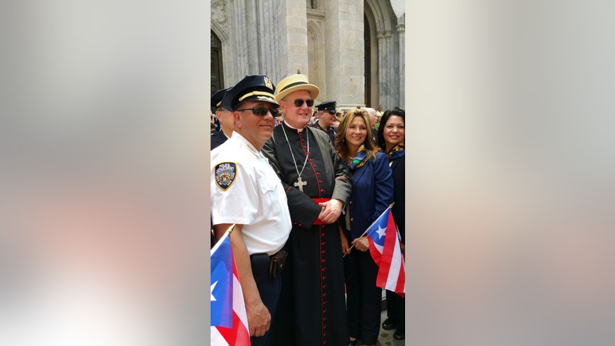 Roman Catholic Cardinal Timothy Dolan sports a straw hat while greeting marchers in front of St. Patrick's Cathedral as the annual National Puerto Rican Day Parade makes its way up New York's Fifth Avenue, Sunday,  June 14, 2015. Hundreds of thousands of people turned out for the parade which celebrates the heritage and identity of Puerto Ricans living in New York. (AP Photo/Verena Dobnik)