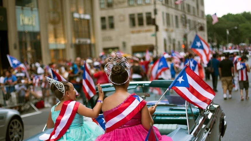 Kaylee Vazquez, 8, left, and Jayda Vazquez, 12, ride atop a convertible as the annual National Puerto Rican Day Parade makes its way up New York's Fifth Ave., Sunday, June 14, 2015. Hundreds of thousands of people turned out for the parade which celebrates the heritage and identity of Puerto Ricans living in New York. (AP Photo/Kevin Hagen)