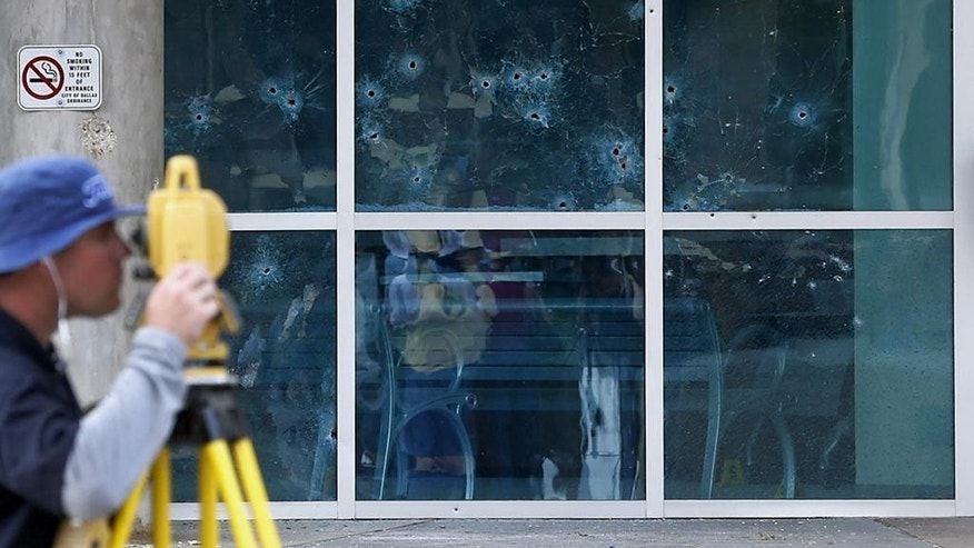 June 13, 2015: With bullet holes in the side of the Dallas Police headquarters, Bill Smith of the FBI works the scene after an early morning shooting in Dallas.