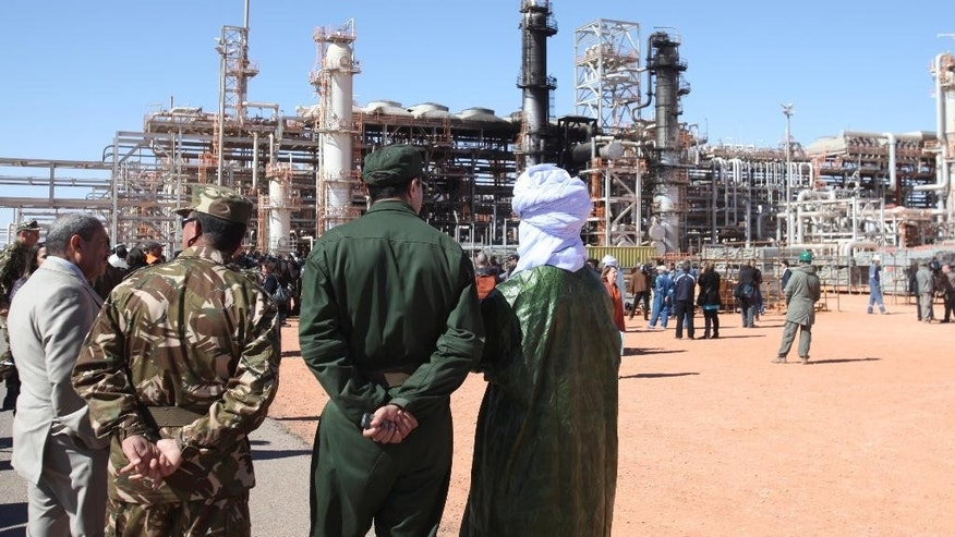 FILE - In this Jan. 31, 2013 file photo, Algerian soldiers and officials stand in front of the gas plant in Ain Amenas, seen in background, during a visit organized by the Algerian authorities for news media. The U.S. said the military launched an airstrike Saturday, June 13, 2015, targeting an al-Qaida leader in eastern Libya who has been charged with leading the attack on the gas plant in Algeria in 2013 that killed 35 hostages, including three Americans. The Libyan government and U.S. officials said warplanes targeted and likely killed Mokhtar BelMokhtar and several others. (AP Photo, File)