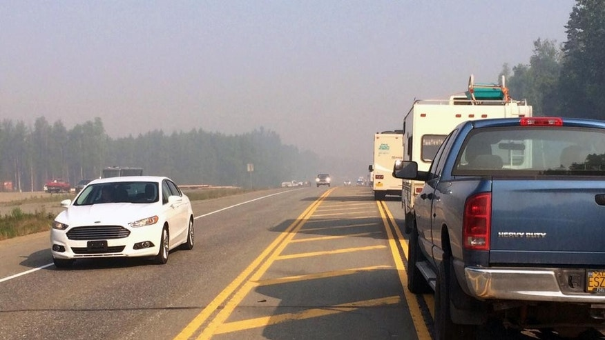 Northbound traffic is backed up on the Parks Highway near Willow, Alaska, on Monday, June 15, 2015, as state troopers allow southbound traffic to move through a wildfire area. The wildfire north of Anchorage shut down a key highway and forced the evacuation of 1,700 structures after it mushroomed in size from just two acres Sunday afternoon to more than 10 square miles by early Monday, officials said. (AP Photo/Mark Thiessen)