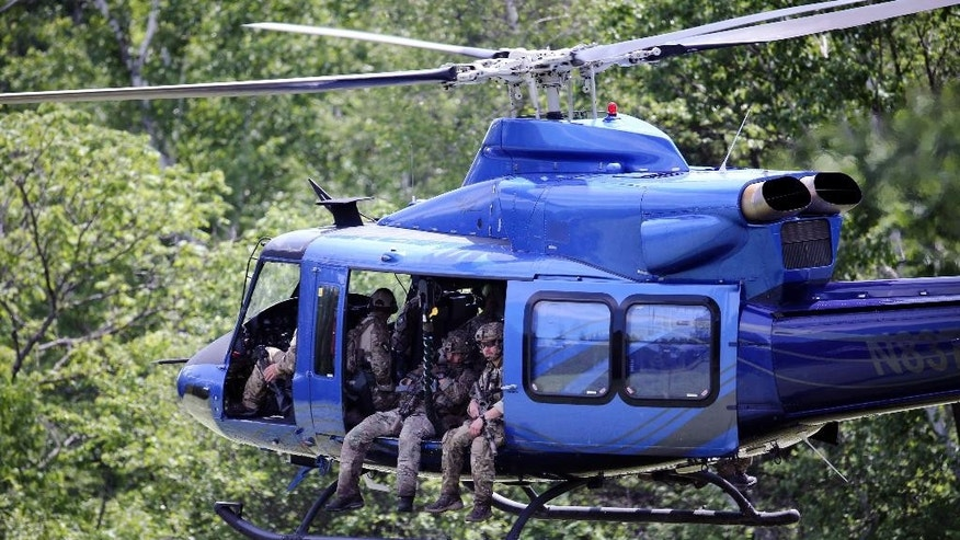 A law enforcement helicopter takes off from a backyard after picking up team members who searched a wooded area near the Saranac River on Sunday, June 14, 2015, in Saranac, N.Y. Law enforcement personnel are in the ninth day of searching for David Sweat and Richard Matt, two killers who used power tools to cut their way out of Clinton Correctional Facility in Dannemora in northern New York. (AP Photo/Mike Groll)