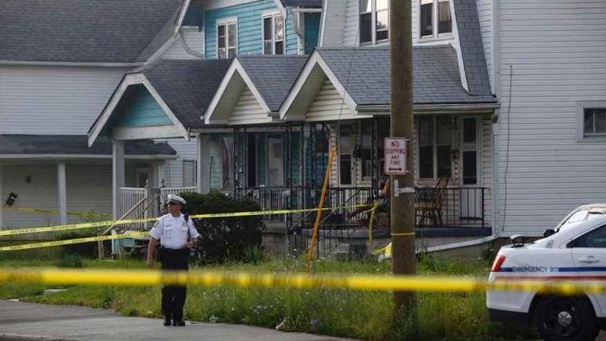 June 13, 2015: A police officer stands at the scene after multiple people were killed and a teenage girl injured in a shooting inside a home in Columbus, Ohio. (Tom Dodge/The Columbus Dispatch via AP)