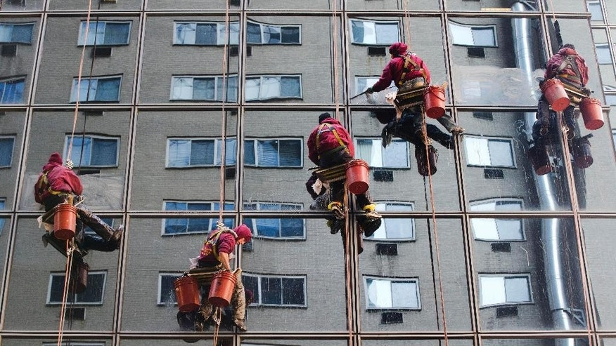 FILE - In this Jan. 16, 2015 file photo, workers with Jenkintown Building Services wash a skyscraper's windows in the Center City section of Philadelphia. Consumers, businesses and investors are facing an era of higher borrowing costs as some of the lowest global interest rates in modern history begin to rise. Yet the message from most economists is a reassuring one: Rates won't likely climb fast or high enough to inflict much damage on economic recoveries in the United States or Europe. (AP Photo/Matt Rourke, File)