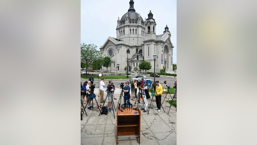 Members of the media wait across the street from the Cathedral of Saint Paul for the announcement of the resignations of Archbishop John Nienstedt and Auxiliary Bishop Lee Anthony Piche during a news conference at the Archdiocese of Saint Paul & Minneapolis Chancery in St. Paul Minn., Monday, June 15, 2015.  In the last two years, Nienstedt was besieged by a clergy sex-abuse scandal that included numerous lawsuits from victims and led to bankruptcy. Then earlier this month, the archdiocese was criminally charged with failing to protect children. (AP Photo/Craig Lassig)