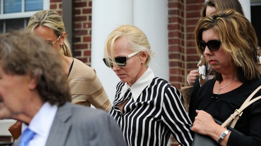 Molly Shattuck,  center, a former Baltimore Ravens cheerleader and the ex-wife of a prominent Maryland energy executive, leaves the Sussex County Courthouse Tuesday, June 16, 2015, in Georgetown, Del., after she pleaded guilty to one count of fourth-degree rape, a felony that can carry up to 15 years in jail. Shattuck was indicted last year for rape, unlawful sexual contact and providing alcohol to minors. Sentencing is scheduled for mid-August. (Jason Minto/The Wilmington News-Journal via AP)  NO SALES