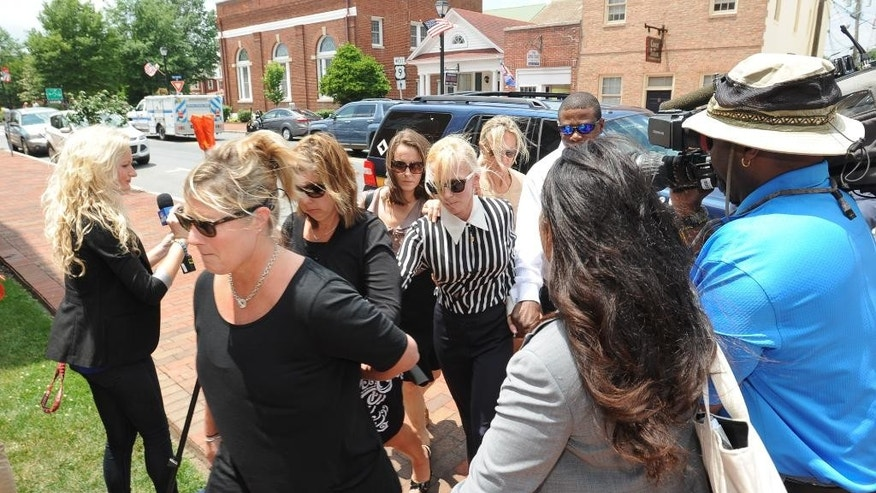 Molly Shattuck,  center, a former Baltimore Ravens cheerleader and the ex-wife of a prominent Maryland energy executive, arrives Sussex County Courthouse Tuesday, June 16, 2015, in Georgetown, Del., where she pleaded guilty to one count of fourth-degree rape, a felony that can carry up to 15 years in jail. Shattuck was indicted last year for rape, unlawful sexual contact and providing alcohol to minors. Sentencing is scheduled for mid-August. (Jason Minto/The Wilmington News-Journal via AP)  NO SALES