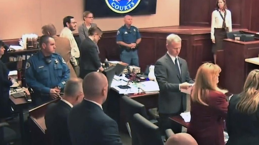 In this image taken from video,  James Holmes' former psychiatrist Dr. Lynne Fenton, far right top,  looks toward Holmes, pictured at top second from left in light-colored shirt and glasses, as all rose for a lunch break during Fenton's testimony in the Holmes trial, in Centennial, Colo., Tuesday, June 16, 2015. The psychiatrist who saw Holmes repeatedly before he carried out his deadly attack on a Colorado movie theater said Tuesday that she had been warned before their first meeting that he said he was thinking of killing people. (Colorado Judicial Department via AP, Pool)
