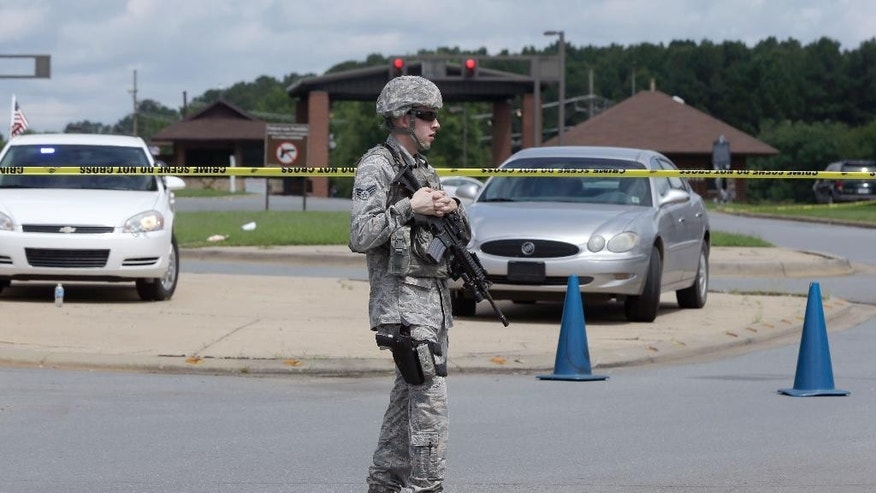 An armed Air Force security guard patrols outside the front gate of little Rock Air Force Base near Jacksonville, Ark., Monday, June 15, 2015.  Military officials said two people were hospitalized after shots were fired when a civilian attempted to enter Little Rock Air Force Base. The Jacksonville police department said the would-be intruder was injured and taken into custody. (AP Photo/Danny Johnston)