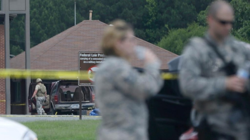 A man, far left, examines an SUV at the front gate of Little Rock Air Force Base near Jacksonville, Ark., Monday, June 15, 2015.  Military officials said two people were hospitalized after shots were fired when a civilian attempted to enter Little Rock Air Force Base. The Jacksonville police department said the would-be intruder was injured and taken into custody. (AP Photo/Danny Johnston)