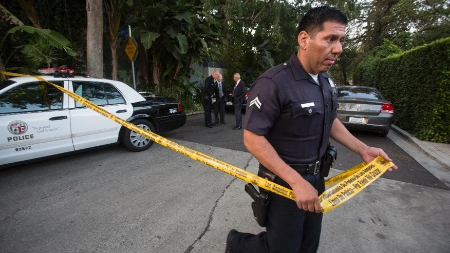 FILE - In this March 31, 2015 file photo, a police officer creates a perimeter outside Andrew Getty's home in the Hollywood Hills area of Los Angeles. Authorities say the oil fortune heir Getty died from an ulcer-related gastrointestinal hemorrhage at his Los Angeles mansion but he also had a toxic level of methamphetamine in his body. The Los Angeles County coroner's report says the death was accidental and cites the meth and heart disease as contributing factors. The April report was obtained Tuesday, June 16, 2015, by The Associated Press and first reported by TMZ.com. (AP Photo/Ringo H.W. Chiu, File)