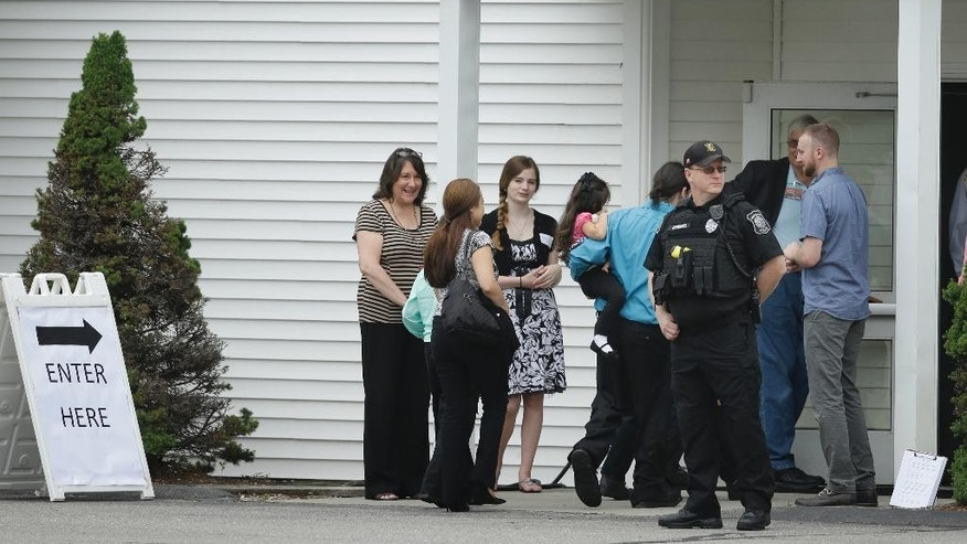 Mourners walk past a Hudson, Mass., law enforcement official, front right, as they enter Grace Baptist Church, Tuesday, June 16, 2015, in Hudson, during a wake for Keith Broomfield who was killed in Syria while fighting the Islamic State group. Broomfield, 36, of Westminster, is believed to be the first U.S. citizen to die fighting alongside Kurdish forces against Islamic State. (AP Photo/Steven Senne)
