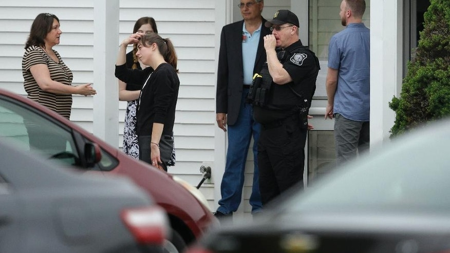 Mourners stand next to a Hudson, Mass., law enforcement official, second from right, near an entrance to Grace Baptist Church, Tuesday, June 16, 2015, in Hudson, during a wake for Keith Broomfield, who was killed in Syria while fighting the Islamic State group. Broomfield, 36, of Westminster, is believed to be the first U.S. citizen to die fighting alongside Kurdish forces against Islamic State. (AP Photo/Steven Senne)