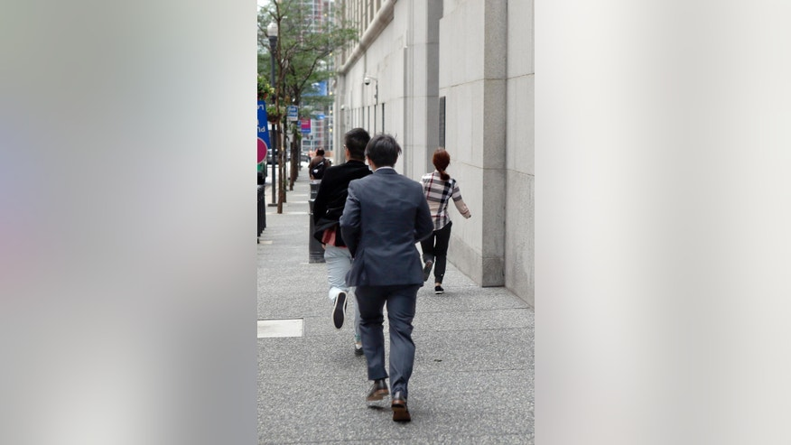 Three Chinese citizens, right, accused of conspiracy involving college entrance exams, run back to federal court to avoid photographers after they were arraigned on charges, Wednesday, June 17, 2015, in Pittsburgh. Four of fifteen Chinese citizens indicted in May were arraigned Wednesday morning in Pittsburgh. The indictment unsealed last month says the suspects either took the tests on behalf of others or paid to have that done for them so they could obtain student visas.  (AP Photo/Keith Srakocic)