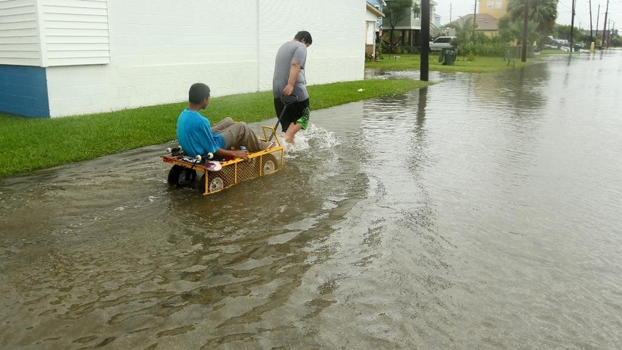 CORRECTS TRANS REF AND CREDIT - Manuel Martinez pulls Jesse McGehee through high water on Saladia Street in Galveston, Texas on Tuesday June 16, 2015. High tides cause by Tropical Storm Bill flooded several low-lying streets. (Jennifer Reynolds/The Galveston County Daily News via AP)