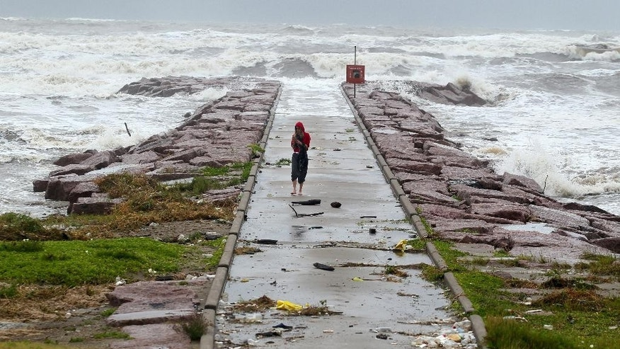 CORRECTS TRANS REF TO TXCOR AND ADDS MBO - A woman walks back from watching the waves roll over the end of the 29th Street Galveston rock groin Tuesday, June 16, 2015, in Galveston, Texas as Tropical Storm Bill makes landfall near Matagorda Bay on the Texas Gulf coast. (Rachel Denny Clow/Corpus Christi Caller-Times via AP)