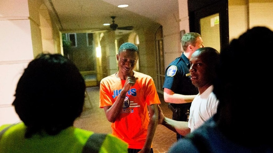A distraught man is comforted as a group of concerned people arrive inquiring about a shooting across the street Wednesday, June 17, 2015, in Charleston, S.C. (AP Photo/David Goldman)
