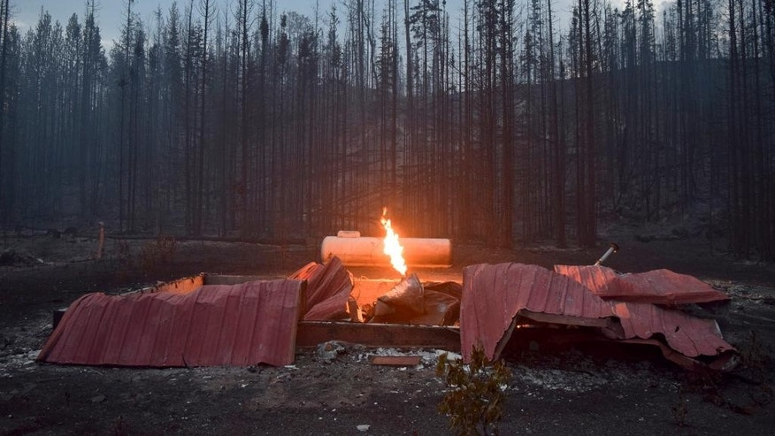 A structure on Slough Avenue burns after the Card Street wildfire burned through the Kenai Key subdivision in Sterling, Alaska on Wednesday, June 17, 2015. The wildfire moved rapidly northeast toward the Kenai National Wildlife Refuge and authorities have evacuated the Upper and Lower Skilak Lake campground. (Rashah McChesney/Peninsula Clarion via AP)