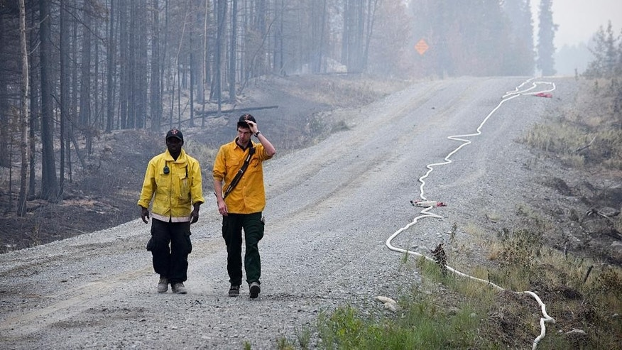 In this June 16, 2015 photo, two Nikiski Fire Department firefighters walk on a road near a fire-ravaged forest left behind by the Card Street fire in Sterling, Alaska. The wildfire moved rapidly northeast toward the Kenai National Wildlife Refuge and authorities have evacuated the Upper and Lower Skilak Lake campground. (Rashah McChesney/Peninsula Clarion via AP)