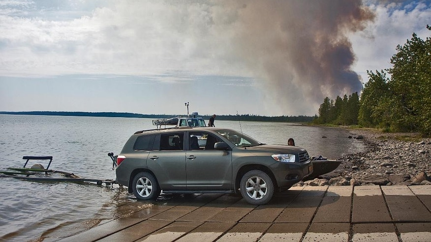 In this June 16, 2015 photo, the Card Street wildfire burns behind the Upper Skilak Campground boat launch as authorities work to evacuate the area near Sterling, Alaska. The wildfire moved rapidly northeast toward the Kenai National Wildlife Refuge and authorities have evacuated the Upper and Lower Skilak Lake campground. (Rashah McChesney/Peninsula Clarion via AP)