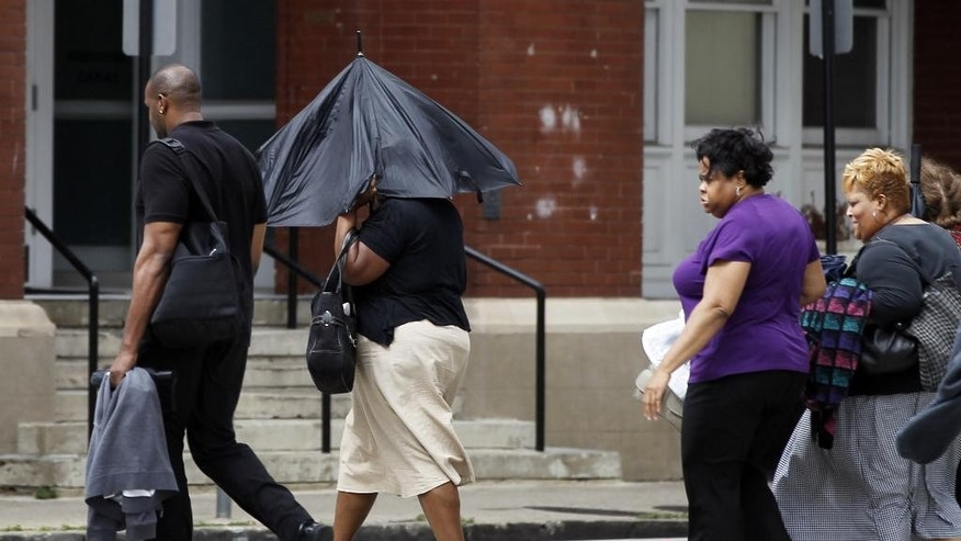 A woman shields herself from strong winds using an umbrella as she and others cross a downtown street Wednesday, June 17, 2015, in Dallas. The remnants of Tropical Storm Bill brought more rain and heavy gust of wind as it passed through the region. (AP Photo/Tony Gutierrez)