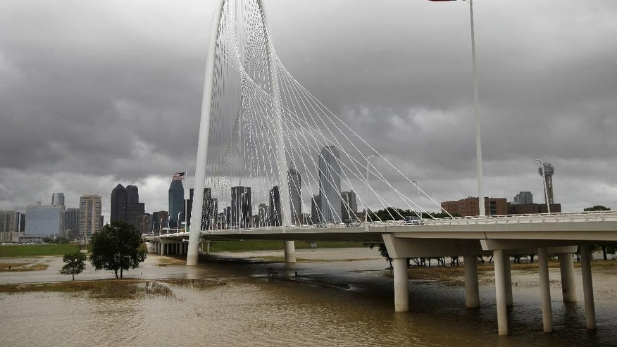 The swollen Trinity river flows beneath the Margaret Hunt Hill bridge as storm clouds pass over the downtown area bringing more rain Wednesday, June 17, 2015, in Dallas. The tropical storm has caused little damage so far in Texas, but authorities warned Wednesday that as Tropical Depression Bill moves northeast, already swollen rivers could overflow their banks and cause more problems for water-weary residents.  (AP Photo/Tony Gutierrez)