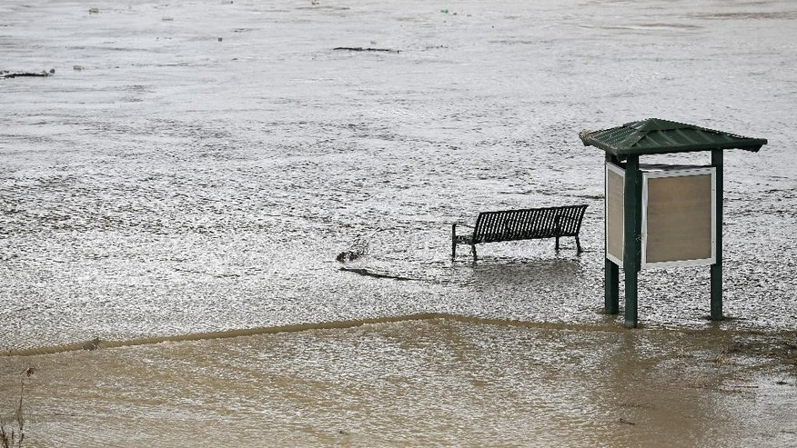 Water flows under a partially submerged park bench along a trail by Skyline Bridge Park on the Trinity river after heavy morning rains Wednesday, June 17, 2015, in Dallas.The tropical storm has caused little damage so far in Texas, but authorities warned Wednesday that as Tropical Depression Bill moves northeast, already swollen rivers could overflow their banks and cause more problems for water-weary residents.  (AP Photo/Tony Gutierrez)