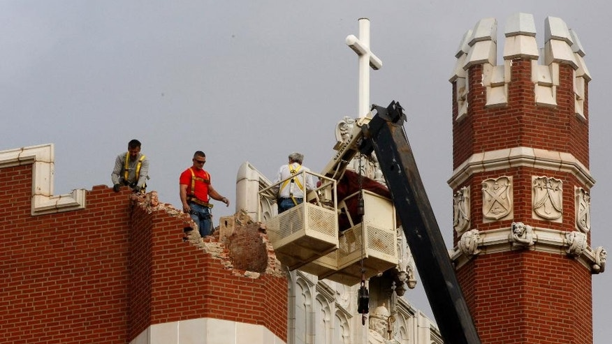FILE - In this Nov. 6, 2011 file photo, maintenance workers inspect the damage to one of the spires on Benedictine Hall at St. Gregory's University following a magnitude-5.0 earthquake in Shawnee, Okla. The more and faster oil and gas companies pump their saltwater waste into the ground, the more they have triggered earthquakes in the central United States, a massive new study from the University of Colorado found. Results were published in the journal Science on Thursday, June 18, 2015. Although Texas, Arkansas, Kansas and other states have seen increases in earthquakes, the biggest jump has been in Oklahoma. (AP Photo/Sue Ogrocki, File)