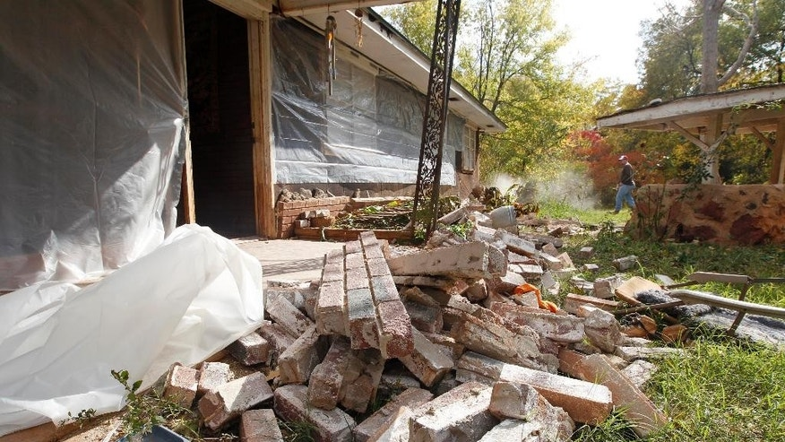 FILE - This Nov. 6, 2011 file photo, Chad Devereaux works to clear up bricks that fell from three sides of his in-laws' home in Sparks, Okla, after two earthquakes hit the area in less than 24 hours. The more and faster oil and gas companies pump their saltwater waste into the ground, the more they have triggered earthquakes in the central United States, a massive new study from the University of Colorado found. Results were published in the journal Science on Thursday, June 18, 2015. Although Texas, Arkansas, Kansas and other states have seen increases in earthquakes, the biggest jump has been in Oklahoma. (AP Photo/Sue Ogrocki,File)
