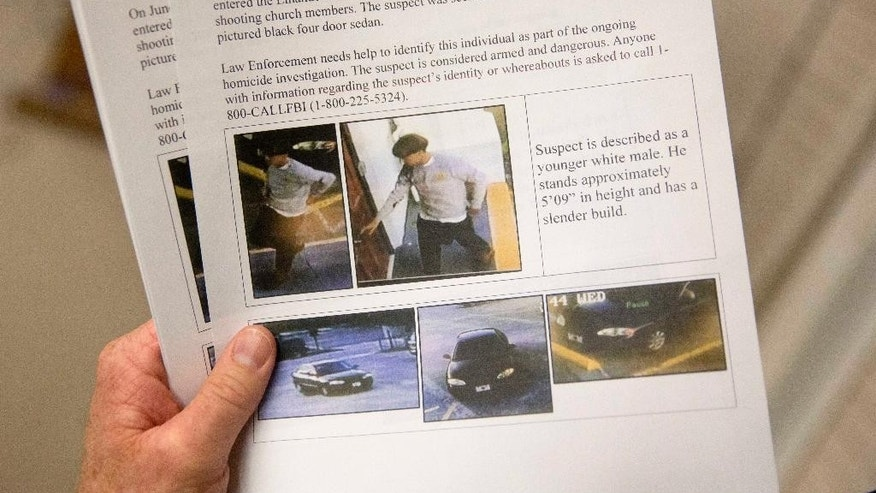 Charleston Emergency Management Director Mark Wilbert holds a flier distributed to media, Thursday, June 18, 2015, with surveillance footage of a suspect wanted in the connection of a shooting Wednesday at Emanuel AME Church during a news conference, in Charleston, S.C. (AP Photo/David Goldman)