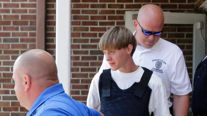Charleston, S.C., shooting suspect Dylann Storm Roof, center, is escorted from the Shelby Police Department  in Shelby, N.C., Thursday, June 18, 2015. Roof is a suspect in the shooting of several people Wednesday night at the historic The Emanuel African Methodist Episcopal Church in Charleston, S.C. (AP Photo/Chuck Burton)