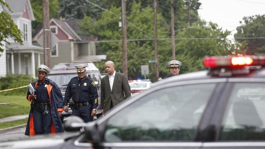 From left: Cincinnati police Lt. Danita Pettis, Chief of Police Jeffrey Blackwell, City Manager Harry Black and assistant police chief David Bailey, survey the scene of the officer-involved shooting on Friday, June 19, 2015 in Cincinnati.  Blackwell says a veteran policeman and an armed person who exchanged gunfire with officers have died.   The officer was identified as 48-year-old Sonny Kim, a 27-year veteran of the department. (Madison Schmidt/The Cincinnati Enquirer via AP)  MANDATORY CREDIT;  NO SALES