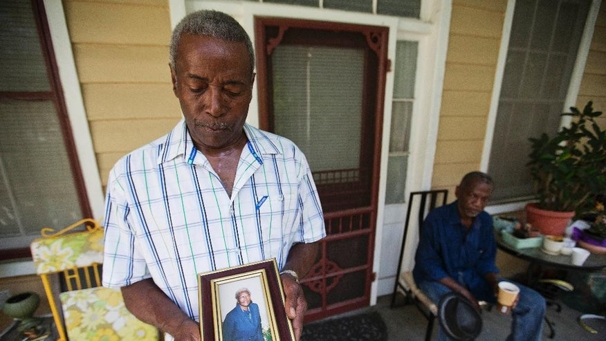 "Walter Jackson, left, holds a photo of his mother Susie Jackson, one of the nine people killed in Wednesday's shooting at Emanuel AME Church, while standing for a portrait on his front porch as his cousin Kenneth Washington, right, looks on Friday, June 19, 2015, in Charleston, S.C. ""Right now all in my heart is anger for him,"" said Jackson. ""I doubt if I'll ever forgive him."" (AP Photo/David Goldman)"