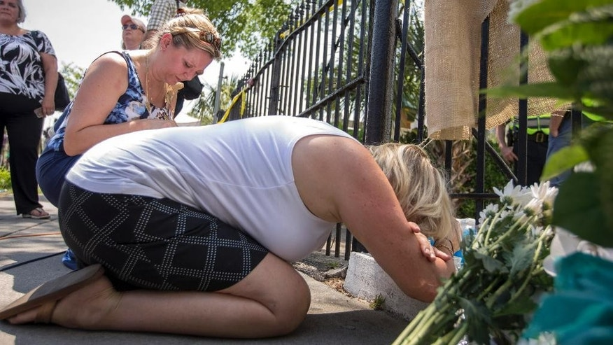 Sisters Kerry Johnson, foreground and Noel Goldman kneel in prayer at the memorial in front of the Emanuel AME Church, Friday, June 19, 2015, Charleston, S.C. The church was the scene of a shooting Wednesday night where Dylann Roof killed nine people including state representative Rev. Clementa C. Pinckney, who was the pastor of the church. (AP Photo/Stephen B. Morton)