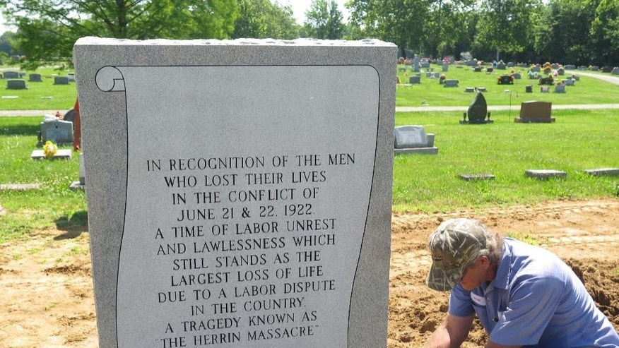 In this June 10, 2015 photo, David Webb of J.W. Reynolds Monuments installs a burial marker commemorating 17 victims of the 1922 Herrin Massacre at the municipal cemetery in the southern Illinois town of Herrin, Ill. A team of local historians and university scientists spent several years working to identify the location of the previously unmarked graves. The clash between striking coal miners and a group of replacement workers and guards was one of the nation's deadliest labor disputes. (AP Photo/Alan Scher Zagier)